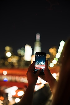 Person taking photo of night city on smartphone