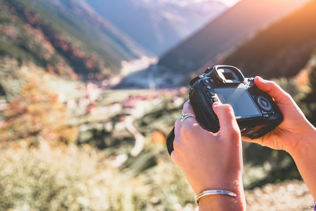 Person taking pictures of the mountains landscape using photo camera during travel