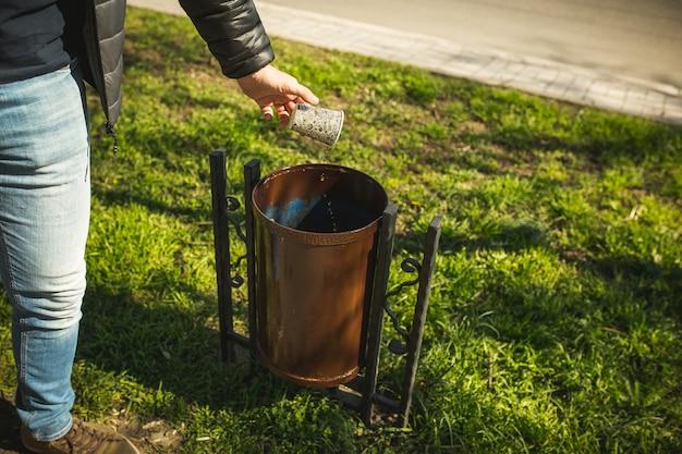 Человек выбрасывает в мусорную корзину бумажную кофейную чашку. не мусорить на улице в городе