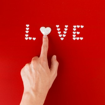 Person touching heart in love inscription