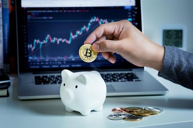 Человек, торгующий или сберегающий криптовалюту с биткойнами и копилкой, и размытие графика цены на компьютере. финансы и технологии