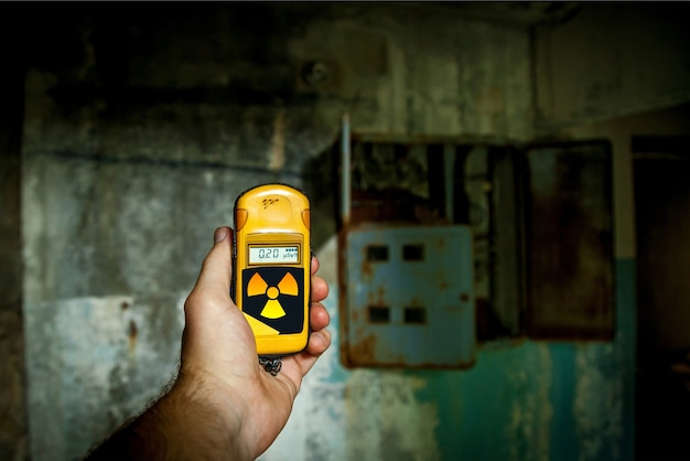 A person tries to check a radiation level with a personal dosimeter near the abandoned building.