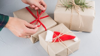 Person tying bow on big gift box