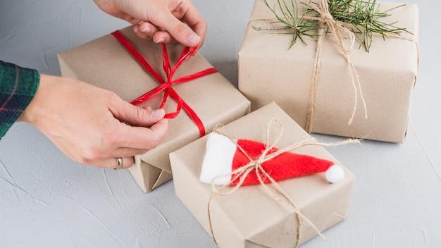 大きな贈り物箱に弓を結ぶ人