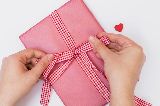 Человек связывает лук на большой розовой подарочной коробке