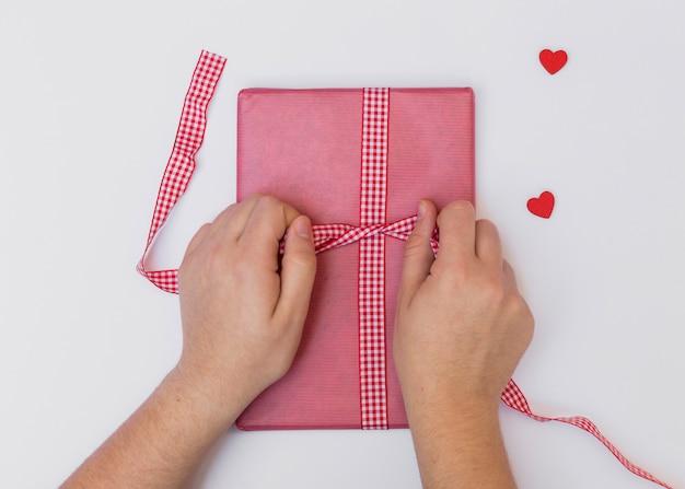Человек связывает лук на розовой подарочной коробке