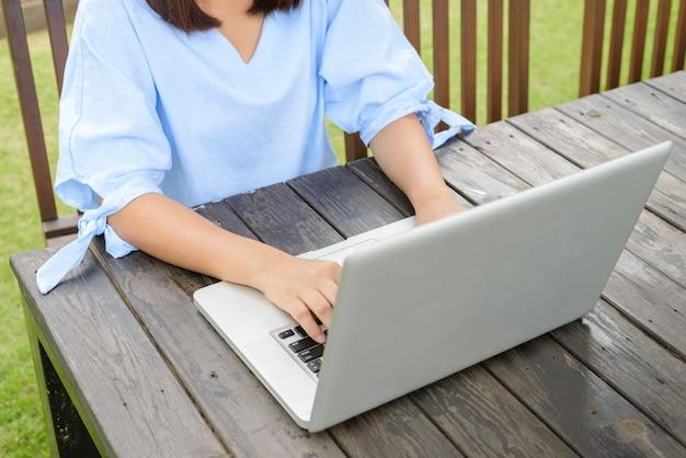 Человек печатать на ноутбуке на деревянном столе