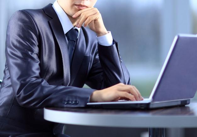 Человек, печатающий на современном ноутбуке в офисе
