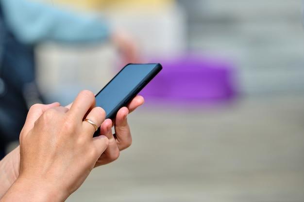 路上でスマートフォンにテキストを入力する人