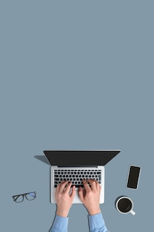 A person uses a laptop on a gray background with a top view and copy space
