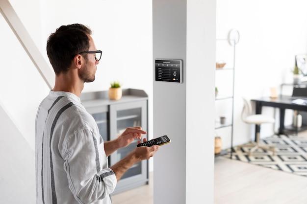 Человек, использующий смартфон в своем автоматизированном доме