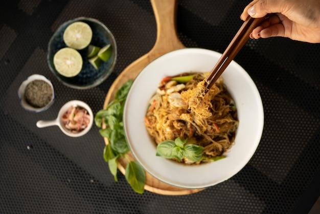麺と背景をぼかした写真を食べる箸を使っている人