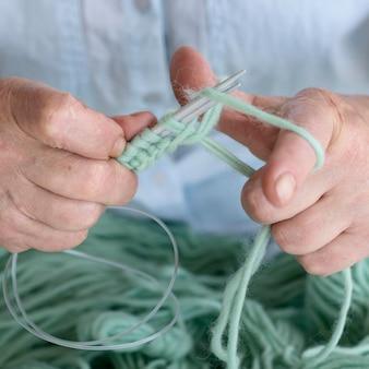 Лицо, использующее иглы для вязания крючком и пряжу