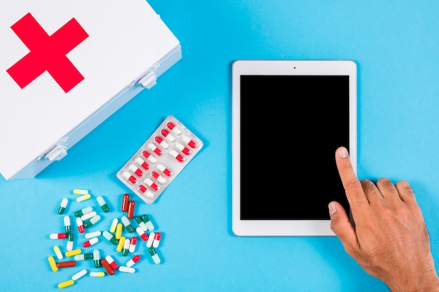 A person using digital tablet with first aid kit and capsules on blue background