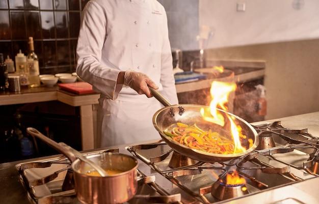 野菜を調理しながらフランベ手順を使用している人