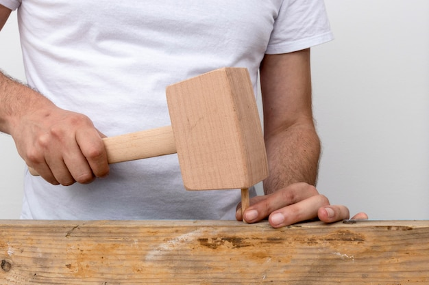 Person using a hammer made out of wood