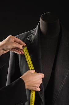 ドレスフォームに巻尺を使用している人