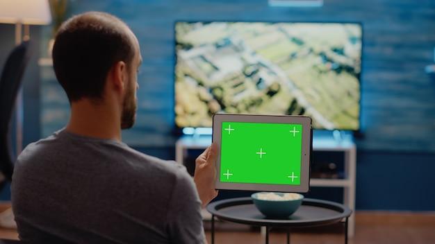 녹색 화면에 현대적인 태블릿을 수평으로 사용하는 사람