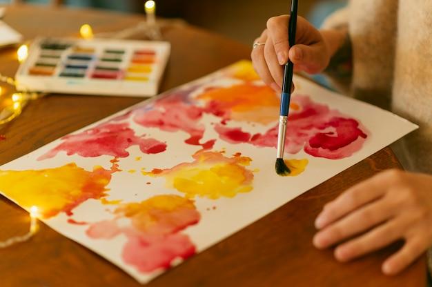 抽象絵画に絵筆を使用している人