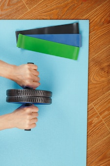 Person using roller on blue mat next to elastic bands