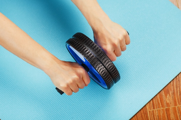 Person using roller on blue mat