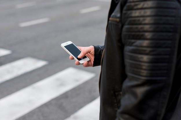 Person using smartphone on road zebra