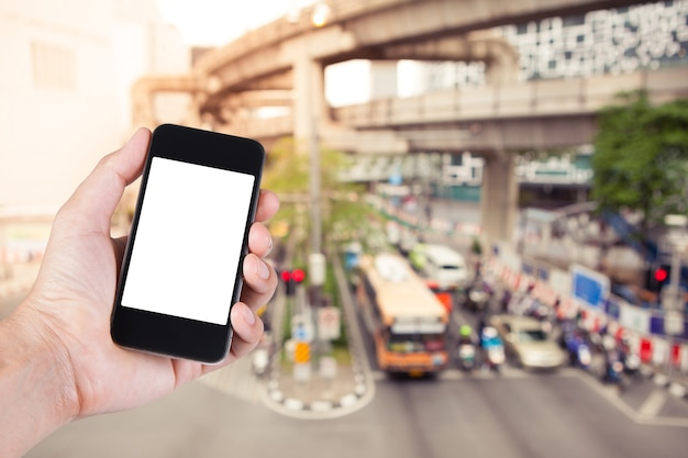 Person using smartphone white screen holder on hand with  blurry of traffic jam on the city street in bangkok thailand.
