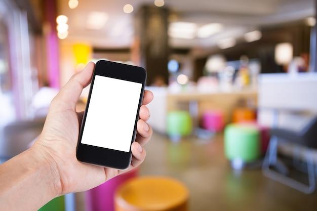 ハンバーガーショップの背景がぼんやりとしたスマートフォンの白いスクリーンホルダーを手にしている人。