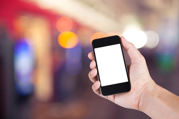 スマートフォンの白いスクリーンホルダーを使用していて、電車駅で歩いている人々の背景がぼんやりとしている人。