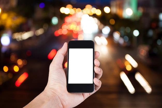 スマートフォンを使用している人は、夜間光で交通のぼやけた背景のボケと手にホワイトスクリーンホルダーを持っています。