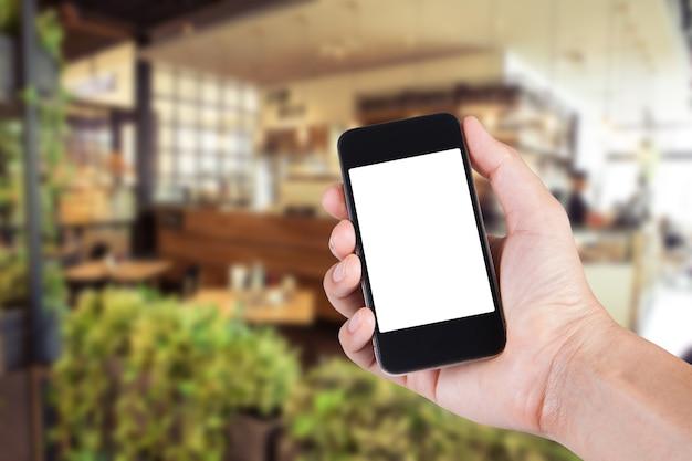 スマートフォンを使用している人は、ぼんやりとした背景のカフェのスクリーンホルダーを持っています。