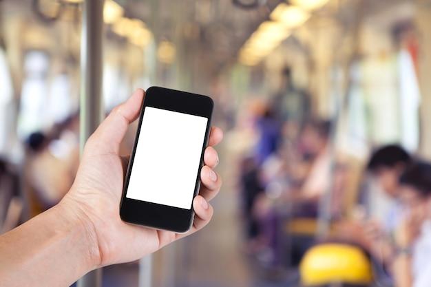 大都市のスカイトレインの乗客のぼやけた背景でスマートフォンの白いスクリーンホルダーを手にしている人。