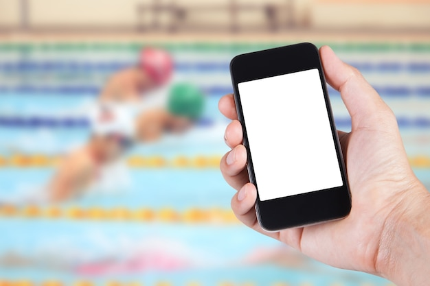 スマートフォンの白いスクリーンホルダーを使用して、スイミングプールの背景がぼやけている人。