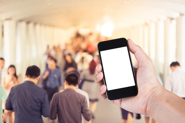 大都市のスカイウォークを歩いている多くの人と手にスマートフォンの白いスクリーンホルダーを使用している人。