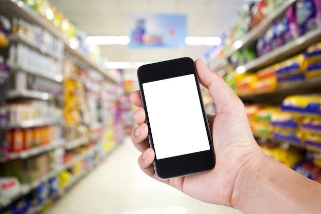 スマートフォンの白いスクリーンホルダーを使って、スーパーマーケットの背景に棚がある人。