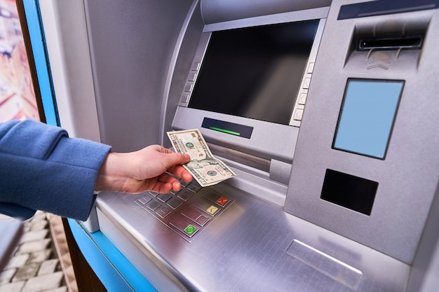 Person using street atm bank to withdraw cash