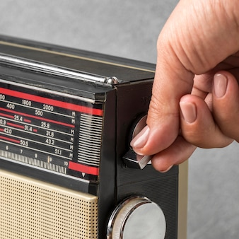 Person using a vintage radio buttons high view