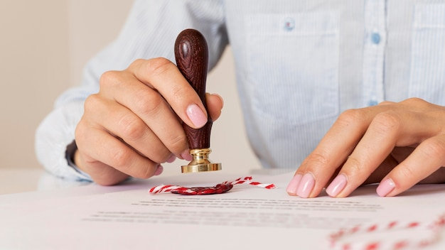 Person using a wax seal blurred certificate