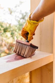 Человек, лакирующий кусок дерева от конструкции дома
