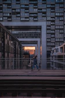 Persona che cammina sul ponte al tramonto