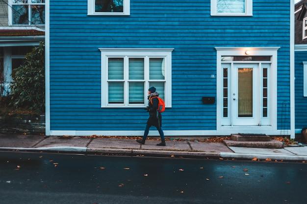 青と白の木造住宅の近くを歩く人