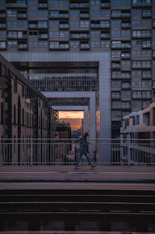 Человек идет по мосту на закате