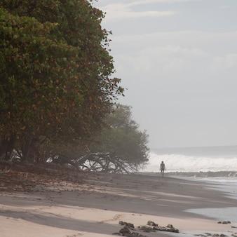 Человек, идущий по пляжу в коста-рике