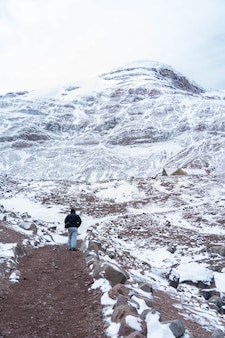 Person walking on snowy chimborazo volcano