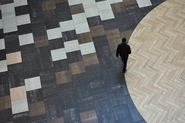 A person walks along a circle of a floor made of colored ceramic tiles.