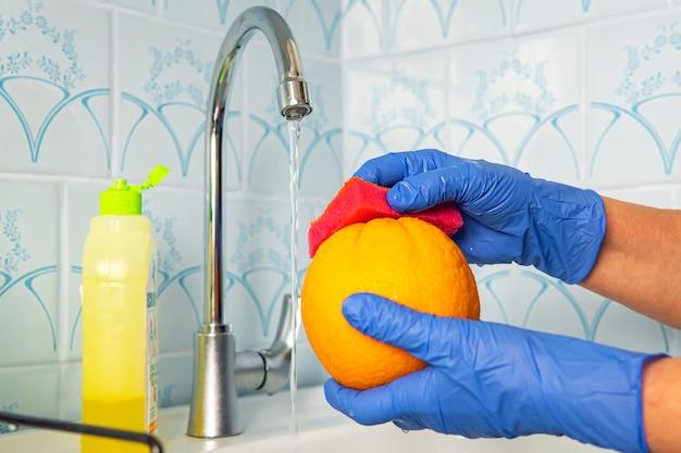 Человек моет фрукты эко-мылом для мытья на кухне с синими стенами. обеззараживание и дезинфекция товаров из магазина. профилактика коронавируса. руки в перчатках моют апельсин.