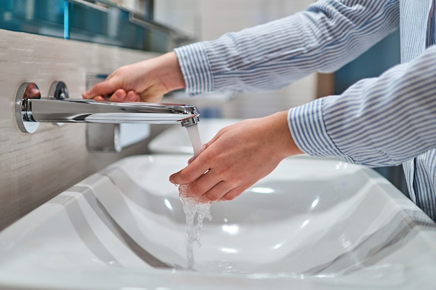 Person washing hands under running water in the bathroom
