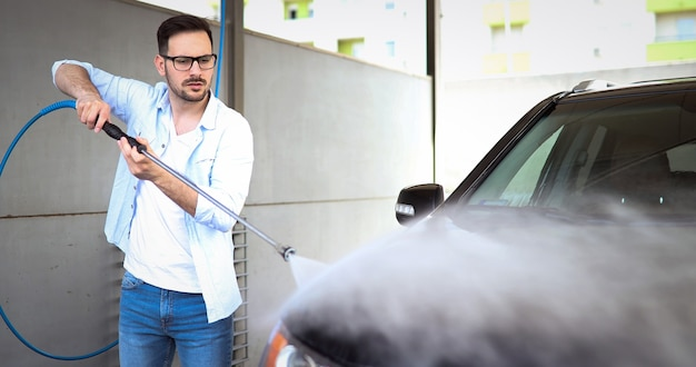 業界のクリーナーでカーウォッシンジェットで車を洗う人