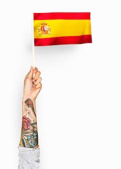 Persona che sventola la bandiera del regno di spagna