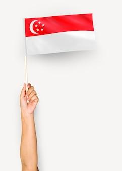 Persona che sventola la bandiera della repubblica di singapore